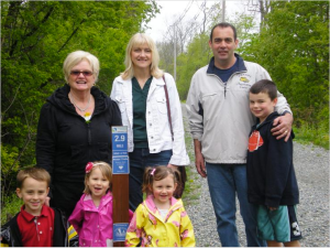Sue Tagg (left) with her grandchildren (front left to right)Preston, Sadie and Chantal. Next to Tagg are sponsors Deborah Sauer and Daniel & Aiden O'Keefe of Danvers Auto Center. The group gathered on the Rail Trail earlier in May with committee members to celebrate the installation of sponsored mile markers on the trail.